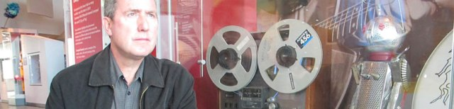 Andy McCluskey with his original 'drummer' Winston behind plexiglas® at the Museum of Liverpool